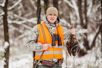 Male hunter in camouflage, armed with a rifle, standing in a snowy winter forest with duck prey