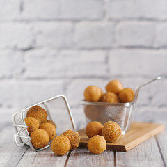 Close-up of fried snacks in metallic baskets on wooden table