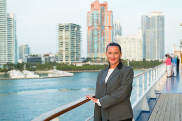 Woman smile in business jacket on shipboard in miami, usa. Sensual woman on ship board on city skyline. Fashion, beauty, look. Travelling for business. Wanderlust, adventure, discovery, journey
