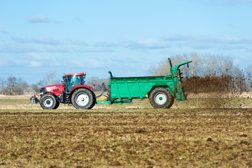 Tractor with manure spreader on the field - 1379
