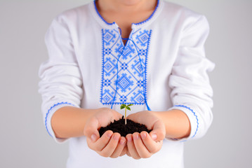 Child holding young plant with soil in hands as Earth Day conception.