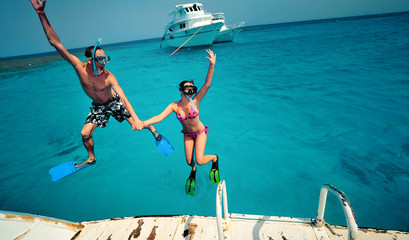Happy young couple having snorkeling and beach fun on the yacht vacation honeymoon travel holidays. Caucasian woman and man playing playful enjoying love. Multiracial couple