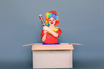Funny kid clown playing in cardboard, shooting party popper confetti. Wall mural