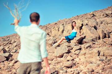Happy young couple having fun in desert sand on vacation honeymoon travel holidays. Caucasian woman and man playing playful enjoying love on date. Multiracial couple