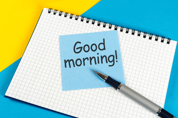 Piece of paper with text Good morning on the yellow-blue table close-up