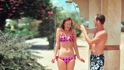 Happy young couple having fun in beach shower on vacation honeymoon travel holidays. Caucasian woman and man playing playful enjoying love on date.