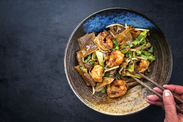 Thai Pad See Ew Noodles with vegetable and king prawns and beef as closeup in a bowl with copy space left
