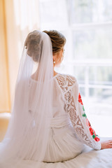 bride in a white dress with lace and embroidery with a veil sits on the bed and looks out the window