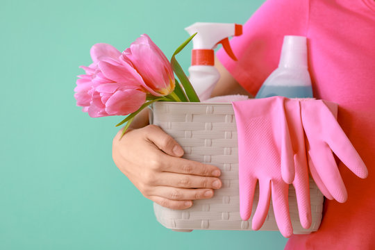 Woman holding basket with cleaning supplies and tulips on color background