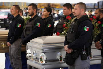 Police agents of the State Attorney General's office observe a minute of silence next to the coffin of late Saul Flores Lares during a ceremony to honor him and a police officer killed by unknown assailants, in Ciudad Juarez