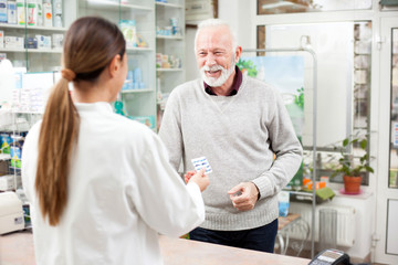 Poster Apotheek Medicine, pharmaceutics, health care and people concept - Happy senior male customer paying for medications at a drugstore