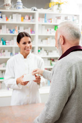 Foto op Canvas Apotheek Medicine, pharmaceutics, health care and people concept - Happy female pharmacist giving medications to senior male customer