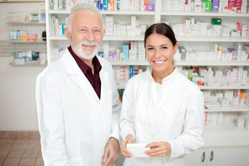 Medicine, pharmaceutics, health care and people concept - Smiling young female and senior male pharmacists in a drugstore. Looking at camera.