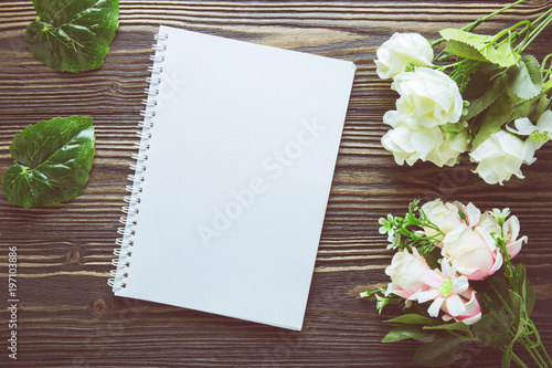 Bouquet of flower and empty diary notebook on rustic wooden table