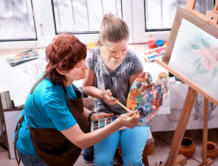 Artist painting easel in studio. Authentic grandmother and kids girl paints with palette watercolor paints palette and brush morning sunlight. Granddaughter teaches grandmother.