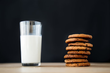 close-up of a cookie with chocolate and a glass of milk on a wooden table on a black background