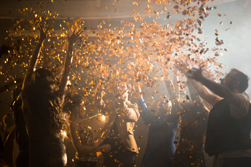 Joyful group of friends dancing to trendy music while hanging out at night club, golden confetti flying in air