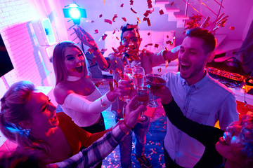 High angle view at group of happy friends enjoying holiday celebration at private house party raising glasses  and toasting under bursts of confetti