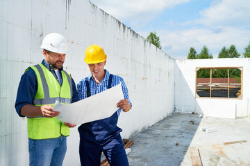 Portrait of two construction workers wearing hardhats and reflective vests  discussing floor plans on demolition site, copy space