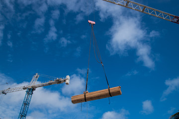 Construction crane lifting pile of wood planks