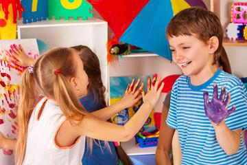 Children painting finger on easel. Small students in art school class. Cheers children in kindergarten. Craft drawing education develops creative abilities of children. Hobby for teenagers.