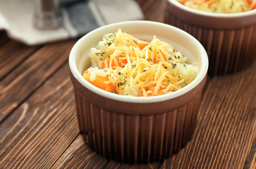 Ramekin with delicious pumpkin risotto on wooden table
