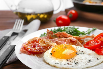 Plate with fried egg, bacon and tomatoes on table, closeup