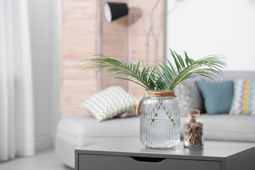 Vase with tropical leaves on table indoors. Interior design element