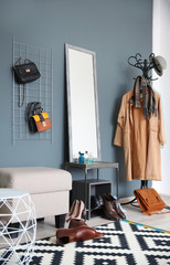 Stylish hallway interior with large mirror and coat rack
