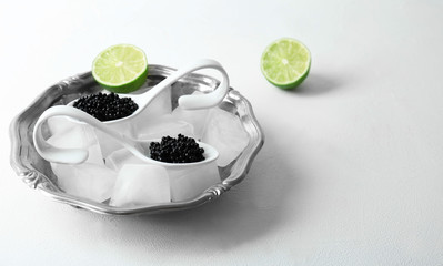 Black caviar served with ice cubes on white background