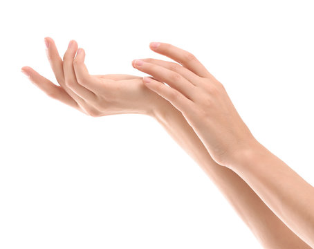 Young woman applying cream onto hands on white background