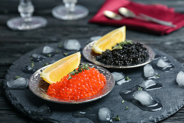 Plates with black and red caviar on table