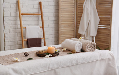 Massage table with towels, candle and sea salt in spa salon