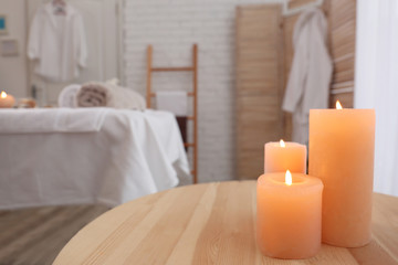 Aroma candles on table in spa salon, closeup