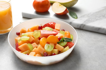 Bowl with fresh fruit salad on table