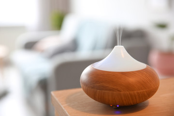 Aroma oil diffuser on table against blurred background
