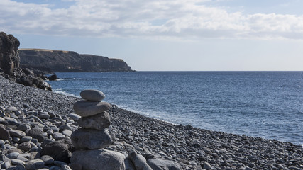 Solitary pebble beach with one rock chairn in a sunny morning, at Playa de San Juan, Tenerife, Canary Islands, Spain