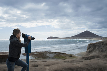 Young Caucasian woman looking through a coin operated binoculars or sightseeing tourist telescope towards El Medano beach and the popular volcanic cone Montana Roja, in Tenerife, Canary Islands, Spain