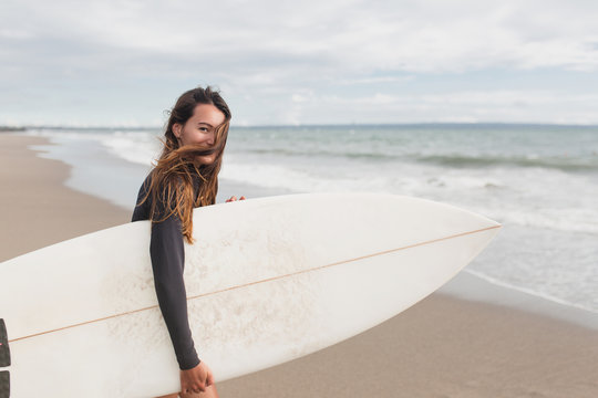 Young adorable woman with long hair and sportive tanned body, smiling and jogging with surf board on the beach in sunny summer day, ready for surfing. Wearing swimsuit