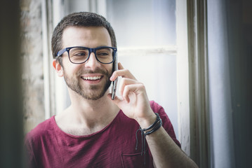 Young attractive man, hipster with glasses, talking on his cell phone, having a nice chat at home