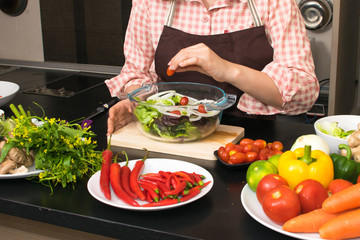 beautiful woman cooking in new kitchen making healthy food with vegetables.