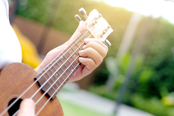 women play ukulele in holiday on grass At the park resort in the morning with sunlight