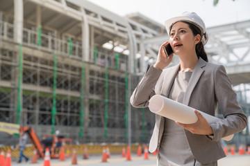 female engineer speak on the phone at building site.