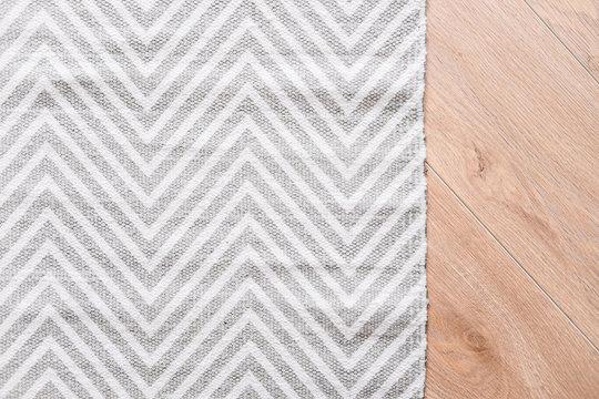 Laminate parquete floor. Light wooden texture. Thin gray and white carpet. Minimalism interior design concept