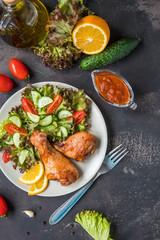 Fried chicken legs and fresh salad on a dark background