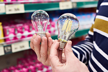 LED and incandescent lamp in hands on store