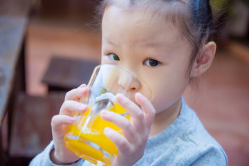 Closeup shot of a little asian girl drinking orange juice from a glass