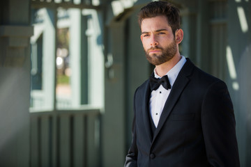 Sharply dressed groom in black tuxedo looking polished, chic, dapper, and dignified