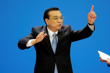 Chinese Premier Li Keqiang gestures as he leaves the news conference following the closing session of the National People's Congress (NPC), at the Great Hall of the People in Beijing