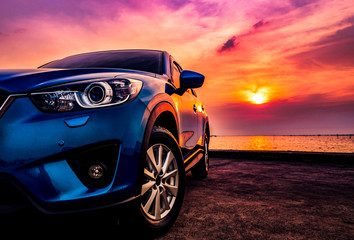 Blue compact SUV car with sport and modern design parked on concrete road by the sea at sunset....